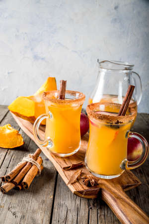 Halloween, Thanksgiving. Traditional autumn, winter drinks and cocktails. Spicy hot pumpkin sangria, with apple, cinnamon, anise. On old rustic wooden table, in glass mugs. Selective focus copy space Stock Photo
