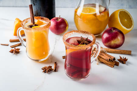 Traditional fall and winter drinks and cocktails. White and red autumn hot spicy sangria with anise, cinnamon, apple, orange, wine. In glass mugs, white marble table. Selective focus copy space Stock Photo