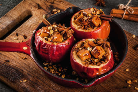 Autumn food recipes. Baked apples stuffed with granola, toffee and spices. On black stone table, in frying pan, copy space Lizenzfreie Bilder