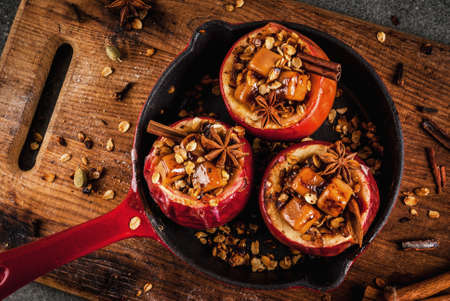 Autumn food recipes. Baked apples stuffed with granola, toffee and spices. On black stone table, in frying pan, copy space top view