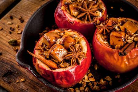 秋の料理レシピ。焼きりんごは、グラノーラ、タフィーとスパイスを詰めた。フライパン、コピーの黒い石のテーブルの上のスペース