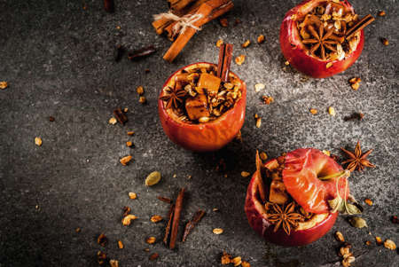 Autumn food recipes. Baked apples stuffed with granola, toffee and spices. On black stone table, copy space top view