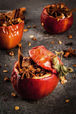 Autumn food recipes. Baked apples stuffed with granola, toffee and spices. On black stone table, copy space