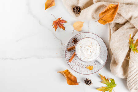 Autumn hot drinks. Pumpkin latte with whipped cream, cinnamon and anise on a white marble table, with a sweater (blanket), autumn leaves and fir cones. Copy space top view