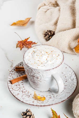 Autumn hot drinks. Pumpkin latte with whipped cream, cinnamon and anise on a white marble table, with a sweater (blanket), autumn leaves and fir cones. Copy space