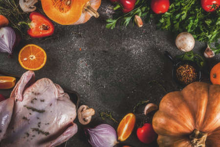 Cooking dinner for christmas, Thanksgiving. Traditional autumn ingredients are vegetables, pumpkin, mushrooms, chicken or turkey, fresh herbs, spices. On a dark table, Top view copy space, frame
