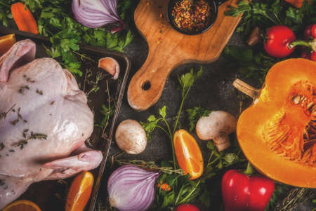 Cooking dinner for christmas, Thanksgiving. Traditional autumn ingredients are vegetables, pumpkin, mushrooms, chicken or turkey, fresh herbs, spices. On a dark table, Top view copy space