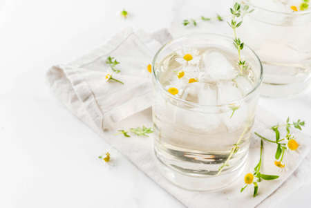 Summer refreshing drinks, infused herbal water, iced tea. Chamomile Honey and Whiskey Cocktail with thyme in glasses, on a white marble table. Copy space Stock Photo