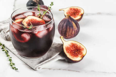 Iced autumn cocktail with red wine, thyme and figs, on white marble table, copy space