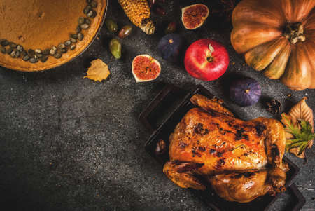 Thanksgiving Day food. Roasted whole chicken or turkey with autumn vegetables and fruits: corn, pumpkin, pumpkin pie, figs, apples, on dark grey background, top view  copy space