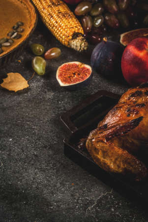 Thanksgiving Day food. Roasted whole chicken or turkey with autumn vegetables and fruits: corn, pumpkin, pumpkin pie, figs, apples, on dark grey background, copy space