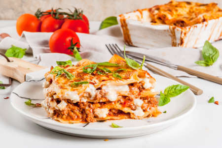 Italian food recipe. Dinner with classic lasagna bolognese with béchamel sauce, parmesan cheese, basil and tomatoes, on white marble table, coopy space Foto de archivo