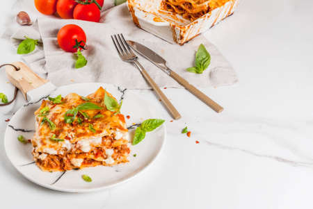 Italian food recipe. Dinner with classic lasagna bolognese with b�chamel sauce, parmesan cheese, basil and tomatoes, on white marble table, coopy space Reklamní fotografie