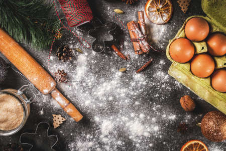 Christmas, New Year holiday cooking background. Ingredients, spices, dried oranges and baking molds, Christmas decorations (balls, fir-tree branch, cones), On black stone table, copy space top view
