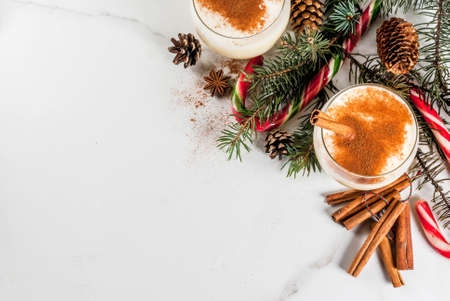 Traditional winter and Christmas drink eggnog with grated nutmeg, anise stars and cinnamon. On white marble table, with spices, christmas tree, pine cones, candy cane, copy space top view Stock Photo