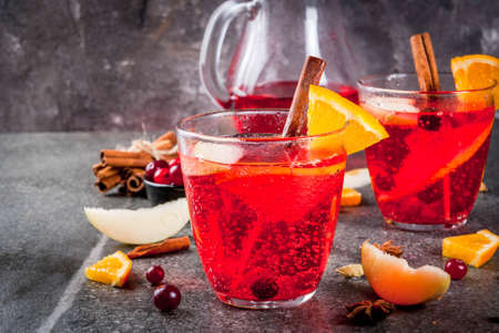 Fall and winter cold drinks, cranberry and orange holiday christmas punch with cinnamon, anise stars,  on black background copy space Stock Photo