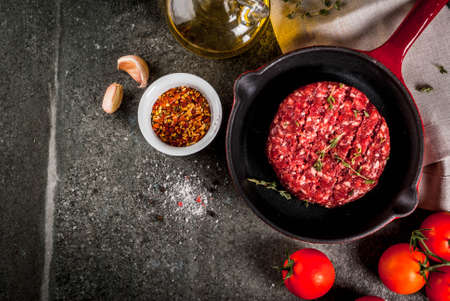 Raw organic beef meat burgers cutlets  with spices, thyme, tomatoes, olive oil in frying pan on black background, top view copy space