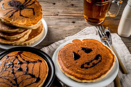 Ideas for breakfast are Halloween, food for children. Pumpkin pie pancakes decorated with chocolate syrup in a traditional style - spider web, spider, jack lantern. On wooden rustic table, copy space