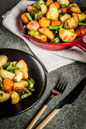Teller und Pfanne mit gebratenem Gemüse der Saison Herbst (Zucchini, Kartoffeln, Karotten, Bohnen), auf schwarzem Steintisch Kopie Raum Standard-Bild - 87156436