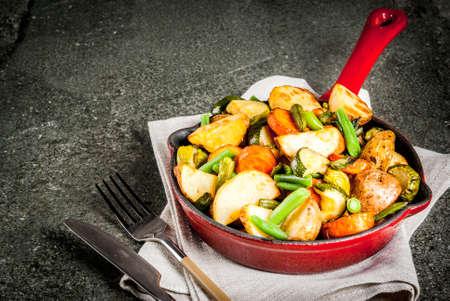 Koekenpan met gefrituurde seizoensgebonden herfstgroenten (courgette, aardappelen, wortelen, bonen), op zwarte stenen tafel kopie ruimte bovenaanzicht Stockfoto