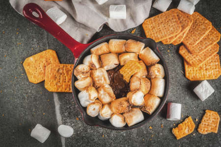 Indoor s'mores, baked s'mores dip in a cast iron skillet pan with graham crackers., dark grey table, copy space top view