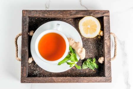 Cup of ginger tea with lemon,fresh mint and honey, in wooden tray, on white marble table, copy space top view Stockfoto