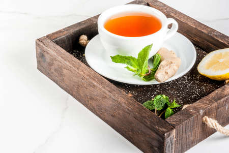Cup of ginger tea with lemon,fresh mint and honey, in wooden tray, on white marble table, copy space