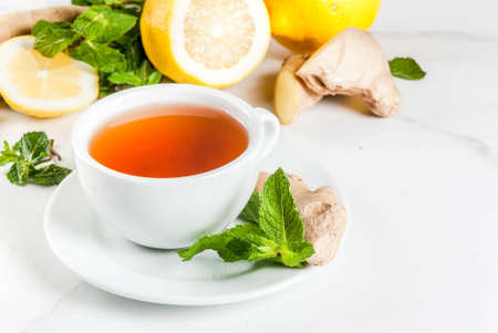 Cup of ginger tea with lemon,fresh mint and honey, on white marble table, copy space