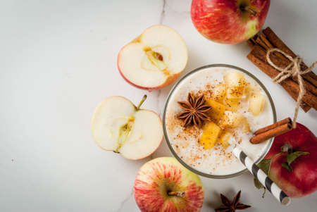 Healthy vegan food. Dietary breakfast or snack. Apple pie smoothies, with apples, yogurt, cinnamon, spices, walnuts. In a glass, on a white marble table. Copy space top view