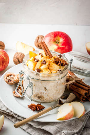 Healthy vegan food. Dietary breakfast or snack. Apple pie overnight oats, with apples, yogurt, cinnamon, spices, walnuts. In a glass, on a white marble table. Copy space