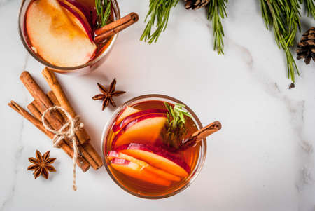 Christmas, Thanksgiving drinks. Autumn, winter cocktail grog, hot sangria, mulled wine - apple, rosemary, cinnamon, anise. On white marble table. With cones, rosemary. Copy space top view