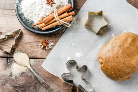 Christmas baking. Ginger dough for gingerbread, gingerbread men, stars, Christmas trees, rolling pin, spices (cinnamon and anise), flour. On the home kitchen wooden table. Copy space top view Stock Photo