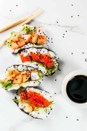 Trend hybrid food. Japanese Asian cuisine. Mini sushi-tacos, sandwiches with salmon, hayashi wakame, daikon, ginger, red caviar. White marble table, with chopsticks, soy sauce. Copy space top view