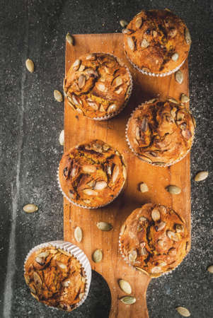 Autumn and winter baked pastries. Healthy pumpkin muffins with traditional fall spices, pumpkin seeds. Black stone table, copy space top view Stockfoto