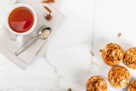 Autumn and winter baked pastries. Healthy pumpkin muffins with traditional fall spices, pumpkin seeds. With tea cup. White marble table, copy space top view