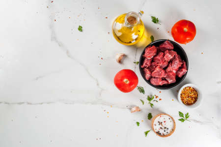 Meat, beef. Fresh raw chopped goulash, beef cubes in a bowl. Spices (salt, pepper), tomatoes, garlic, onions. On a white marble table, with a fork for meat and a knife. Top view copy space Stock Photo