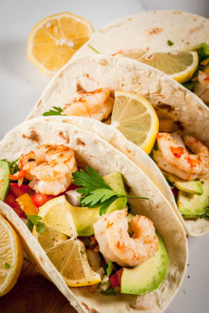 Seafood. Mexican food. Tortilla tacos with traditional homemade salsa salad, parsley, fresh lemon, avocado and grilled shrimp pawns. On a white marble background. Stockfoto