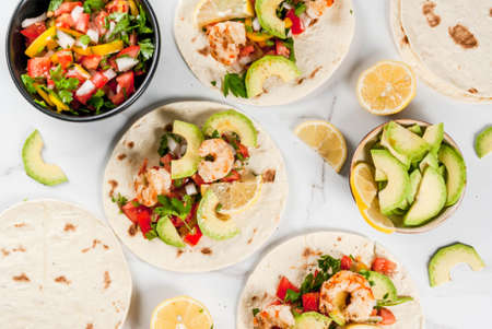 Seafood. Mexican food. Tortilla tacos with traditional homemade salsa salad, parsley, fresh lemon, avocado and grilled shrimp pawns. On a white marble background. Top view copy space Stockfoto