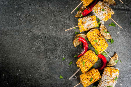 Summer food. Ideas for barbecue and grill parties. Grilled corn grilled on fire. With a sprinkle of cheese (mexican elotes), hot chili pepper and lemon. On a dark stone table. Copy space top view Stockfoto