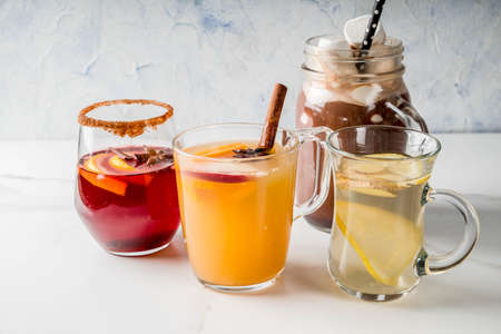 Selection of various autumn traditional drinks: hot chocolate with marshmallow, tea with lemon and ginger, white pumpkin spicy sangria, mulled wine. On white marble table, copy space, selective focus Banque d'images