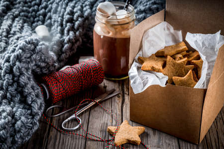 Traditional autumn winter drinks and treats. Cup of hot chocolate with marshmallow and ginger biscuit stars, in gift box, old rustic wooden table. Cozy atmosphere, copy space