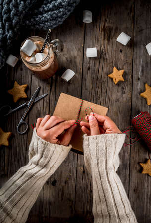 Preparation for the autumn and winter holidays. The person packs the cookies as a gift in a craft box, Christmas ribbon, hands in the frame. Rustic old table, top view copy space