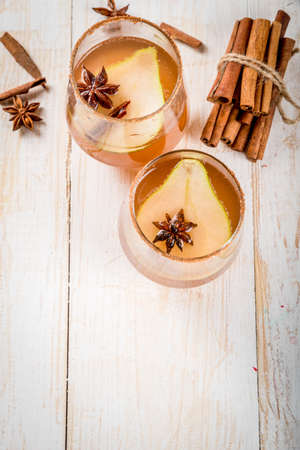 Autumn drinks. Mulled wine. Traditional autumn spicy cocktail with pear, cider and chocolate syrup, with cinnamon, anise, brown sugar. On a white wooden table. Copy space Stok Fotoğraf