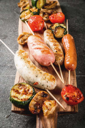 Barbecue. Assortment of various grilled meat sausages, with vegetables BBQ - mushrooms, tomatoes, zucchini, onions. On a black stone table, on cutting board plate, with sauce. Copy space Banque d'images