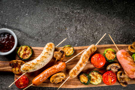 Barbecue. Assortment of various grilled meat sausages, with vegetables BBQ - mushrooms, tomatoes, zucchini, onions. On a black stone table, on cutting board plate, with sauce. Copy space top view