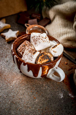 New Year and Christmas treats. Traditional sweets. A cup of hot chocolate with marshmallow fried on fire, gingerbread stars, with sweater on black stone background, copy space Stockfoto