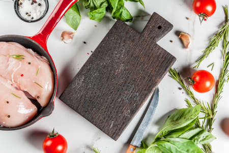 Raw fresh chicken breast fillet with herbs and spices for cooking, in iron cast skillet, white marble table, copy space top view Stok Fotoğraf