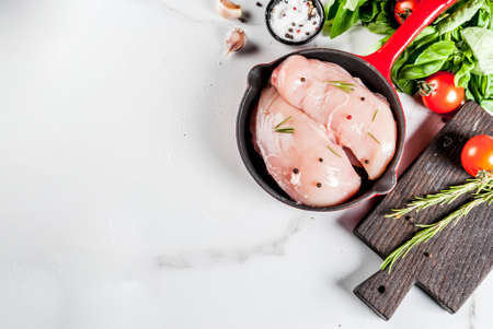 Raw fresh chicken breast fillet with herbs and spices for cooking, in iron cast skillet, white marble table, copy space top view Banque d'images