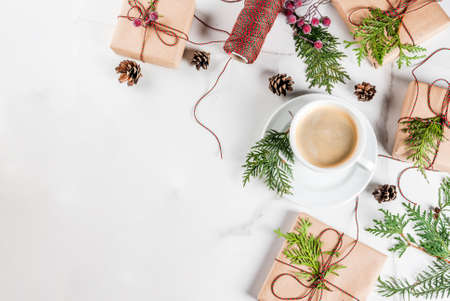 Coffee latte mug with Christmas gift or present box wrapped in kraft paper, decorated with christmas tree branches, pine cones, red berries, on white marble table, copy space top view