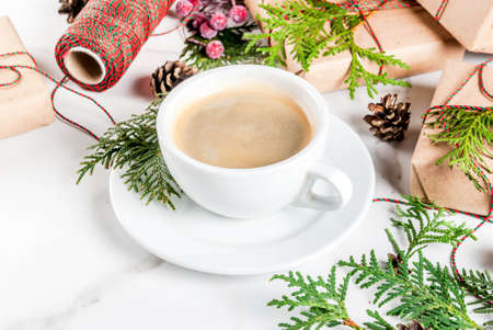 Coffee latte mug with Christmas gift or present box wrapped in kraft paper, decorated with christmas tree branches, pine cones, red berries, on white marble table, copy space Stok Fotoğraf